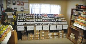 A store with honey, natural fruits and raw beeswax on shelves.